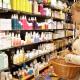 Junge Frau, die in einem Kosmetikgeschäft vor einem Regal steht